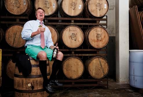 Malcom Gosling posing in front of casks of rum