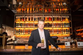 Brian Kinsman standing in front of bar holding drink
