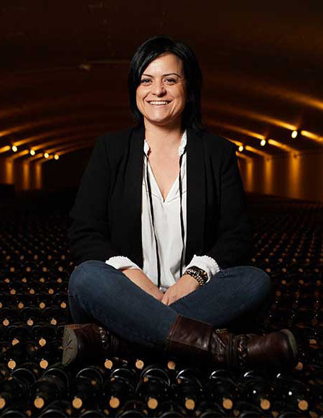 Mercedes García Rupérez sitting on bottles of wine
